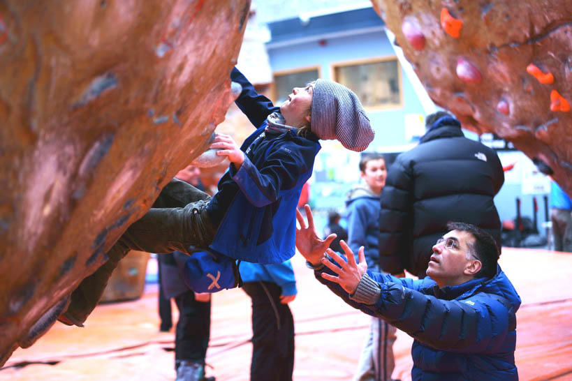 A young climber gets to grips with the wall with adult supervision