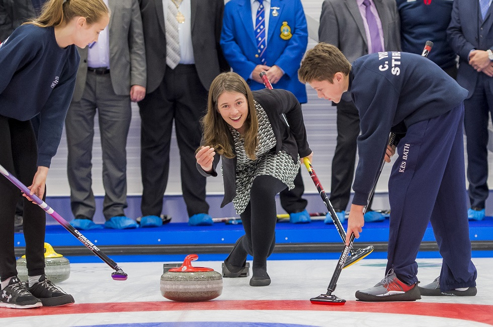 Minister for Public Health and Sport Aileen Campbell throws the first stone at the National Curling Academy with help from Stirling High pupils