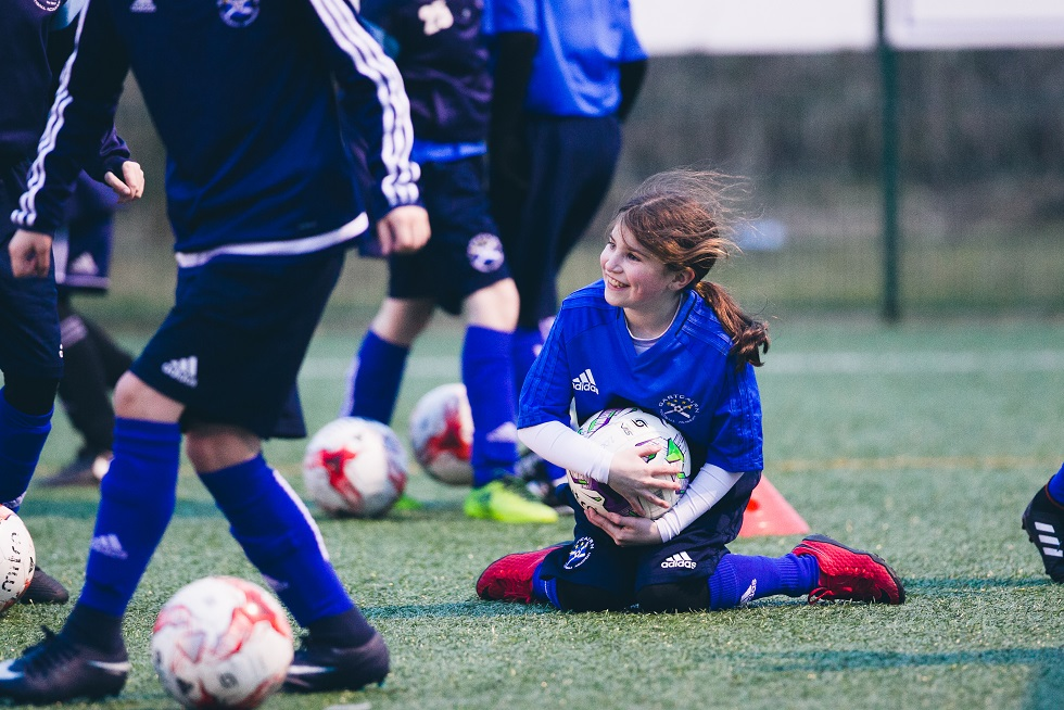 A young player having a ball at training