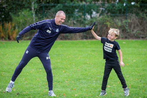 Kenny Miller high fives a young player
