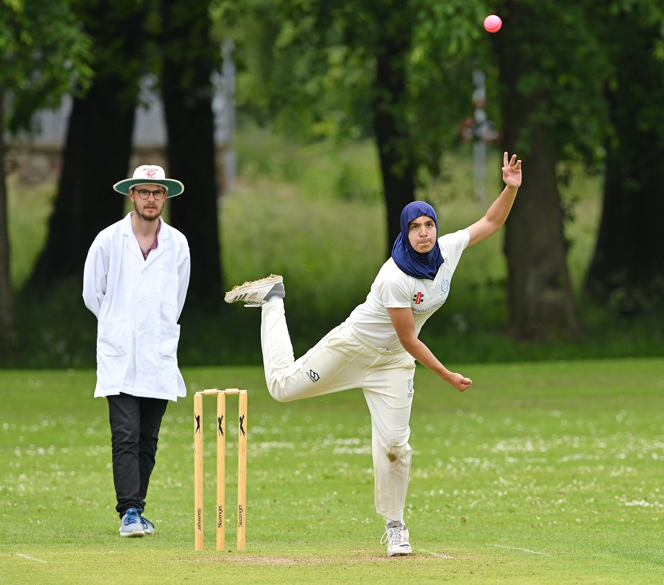 Woman bowling beside umpire in club cricket match