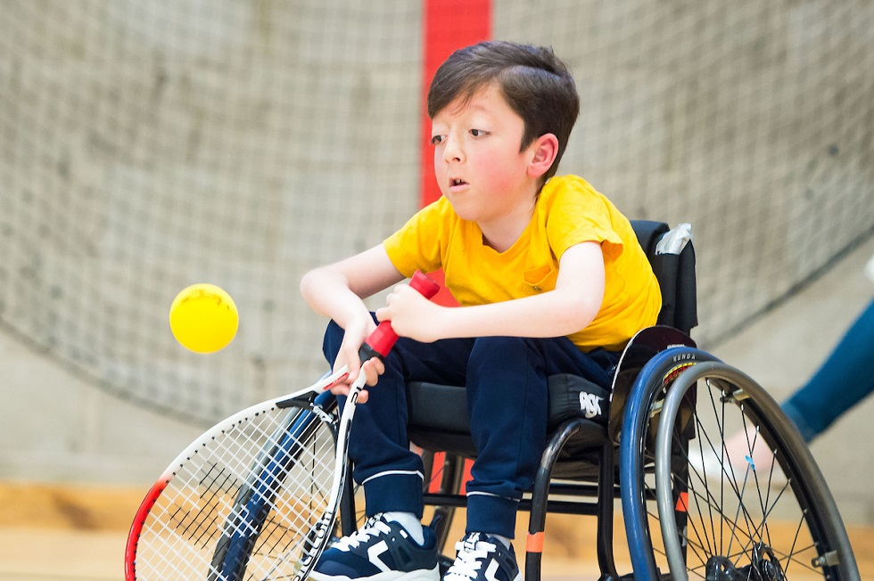 A young male wheelchair tennis participant
